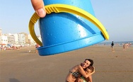 On the beach. A huge blue bucket... or... wait...